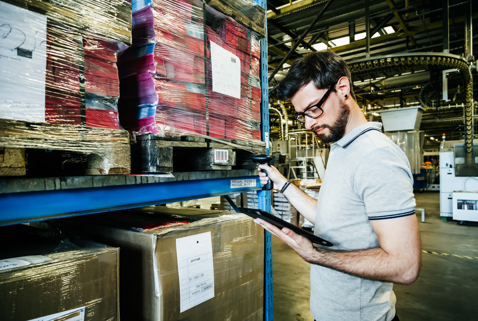 bearded man looks at his clipboard in a warehouse.jpg